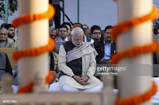 Prime Minister Narendra Modi sitting for prayer meeting after paying homage to Mahatma Gandhi on his 67th death anniversary at Gandhi Smriti on...