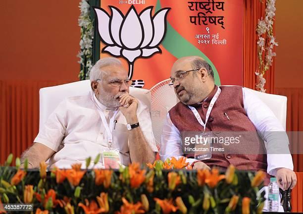 Prime Minister Narendra Modi talking with Bharatiya Janata Party National President Amit Shah during the BJP National Council meeting at Jawaharlal...