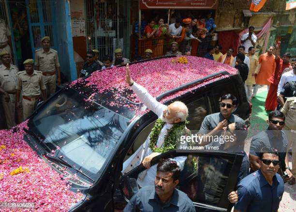 Prime Minister Narendra Modi waves at party supporters as he leaves to file his nomination paper from Varanasi Lok Sabha parliamentary constituency...