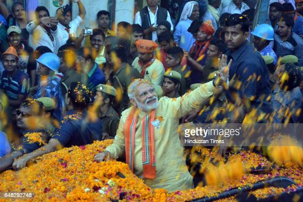 Prime Minister Narendra Modi waves to people during his road show on March 5 2017 in Varanasi India After grand response from the residents of...