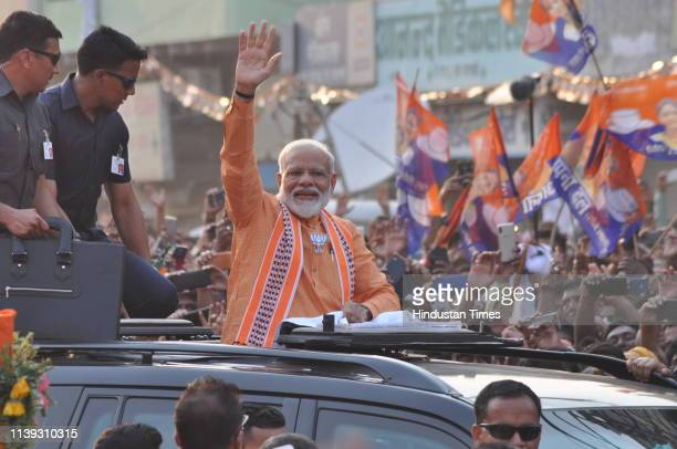 Prime Minister Narendra Modi waves to public during road show at Assi Ghat road on April 25, 2019 in Varanasi, India. PM Modi's cavalcade will pass...