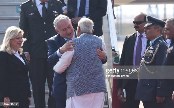 Prime Minister Narendra Modi welcomes Israeli Prime Minister Benjamin Netanyahu with hug as his wife Sara Netanyahu looks on on their arrival at the...