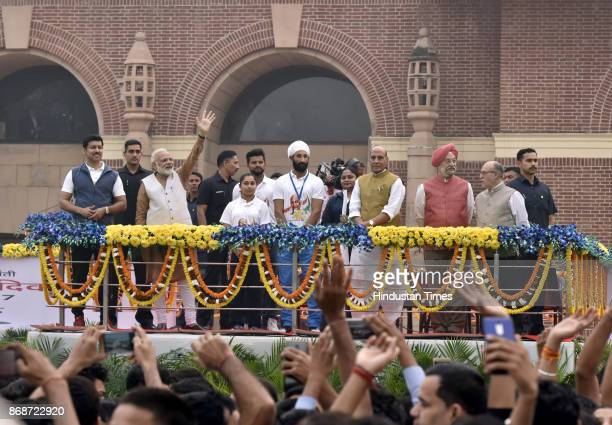 Prime Minister Narendra Modi with Union Home Minister Rajnath Singh wave to the participants during the flagging off ceremony of 'Run for Unity' on...