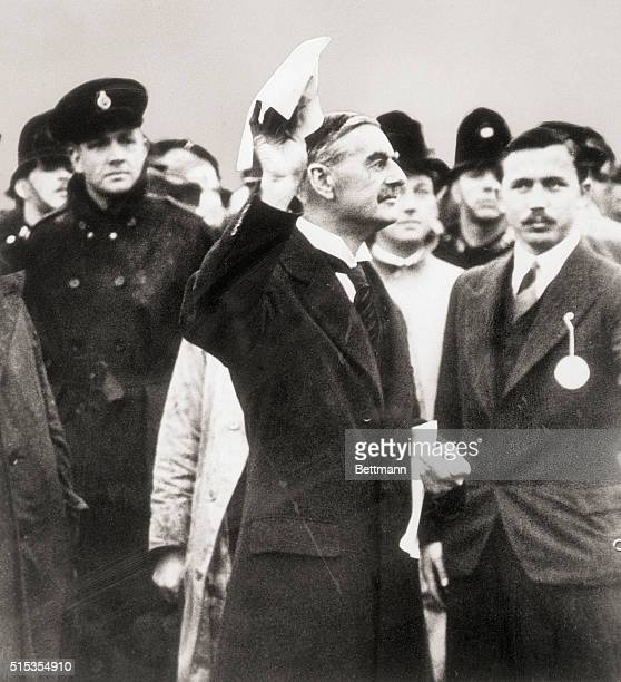 Prime Minister Neville Chamberlain arrives in London holding the Munich Agreement signed by Germany France Great Britain and Italy in Munich