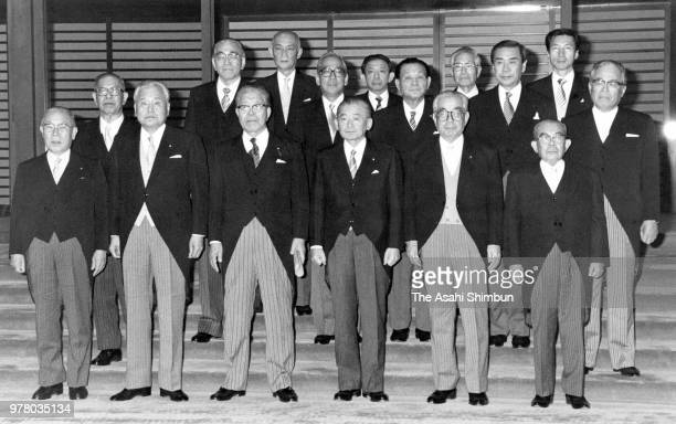 Prime Minister Noboru Takeshita and his new cabinet members pose for photographs after the attestation ceremony at the Imperial Palace on December 27...