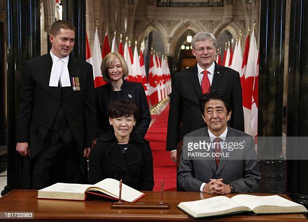 Prime Minister of Canada Stephen Harper and his wif Laureen look on as Prime Minister of Japan Shinzo Abe signs the guest book along with wife Akie...