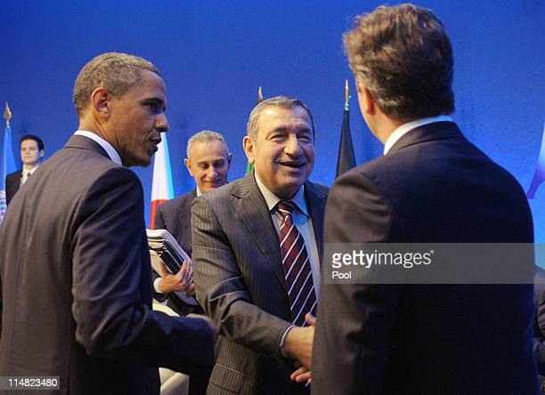 Prime Minister of Egypt Essam Sharaf shakes hands with Prime Minister David Cameron as US President Barack Obama looks on at a meeting with G8...