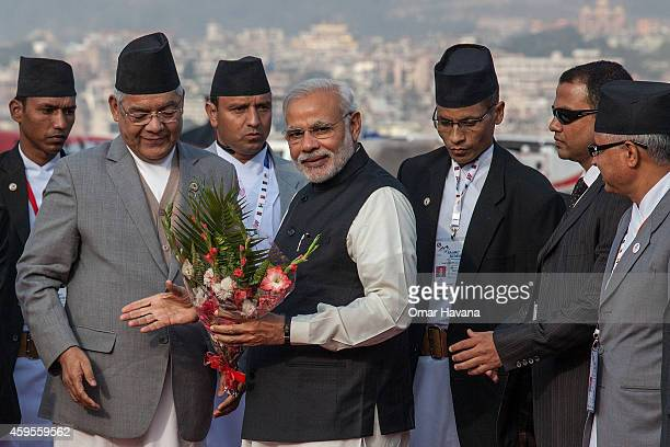 Prime Minister of India Narendra Modi receives a bouquet from Nepali authorities upon his arrival at Tribhuvan Airport for the 18th SAARC Summit on...
