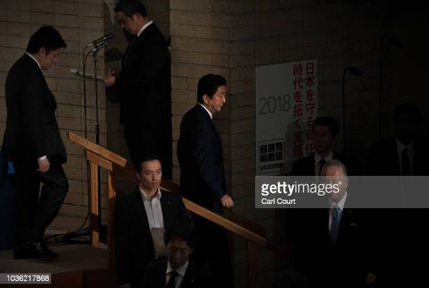 Prime Minister of Japan Shinzo Abe returns to his chair after casting his ballot during a leadership election for the ruling Liberal Democratic Party...