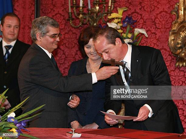Prime Minister of Malta and Head of the Nationalist Party Lawrence Gonzi kisses the cross next to his wife Catherine and Attorney General Silvio...