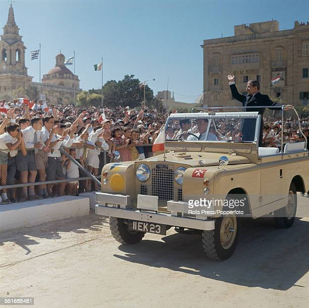 Prime Minister of Malta, Giorgio Borg Olivier waves from the rear platform of an open top Land Rover to crowds of people lining the streets during...