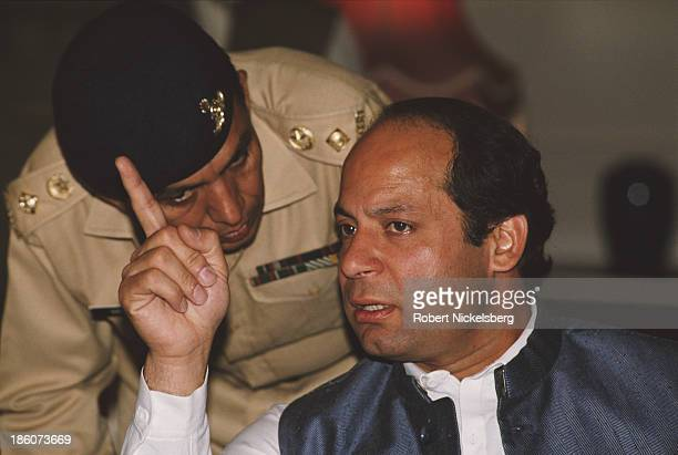 Prime Minister of Pakistan Nawaz Shariftalks to an aide in Pakistan circa 1990