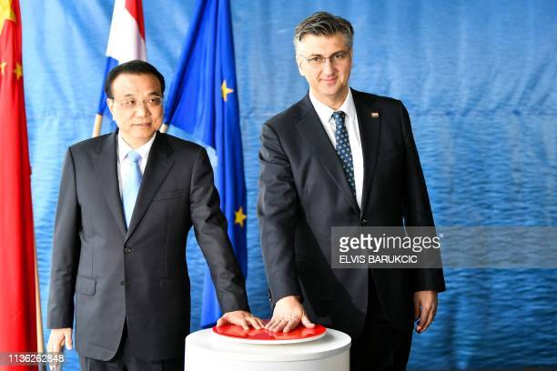 Prime minister of People's Republic of China Li Keqiang and his Croatian counterpart Andrej Plenkovic pose as they push the red button on April 11 in...
