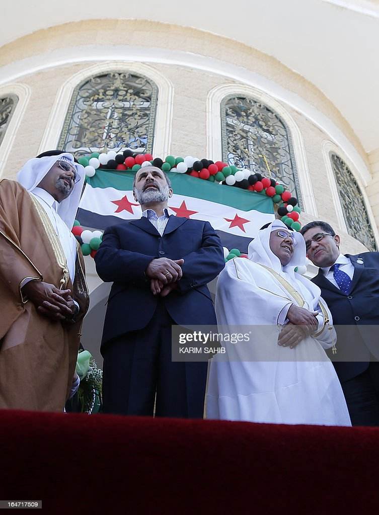 Prime Minister of the interim government of Syria Ghassan Hito (R) and the head of the Syrian opposition delegation, Ahmed Moaz al-Khatib (C) attend the inauguration of the first Syrian interim government embassy to open in Qatar, in the capital Doha on March 27, 2013.