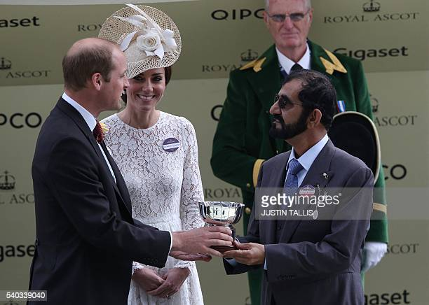 Prime Minister of the United Arab Emirates and ruler of Dubai Sheikh Mohammed bin Rashid alMaktoum is presented with a cup by Britain's Prince...