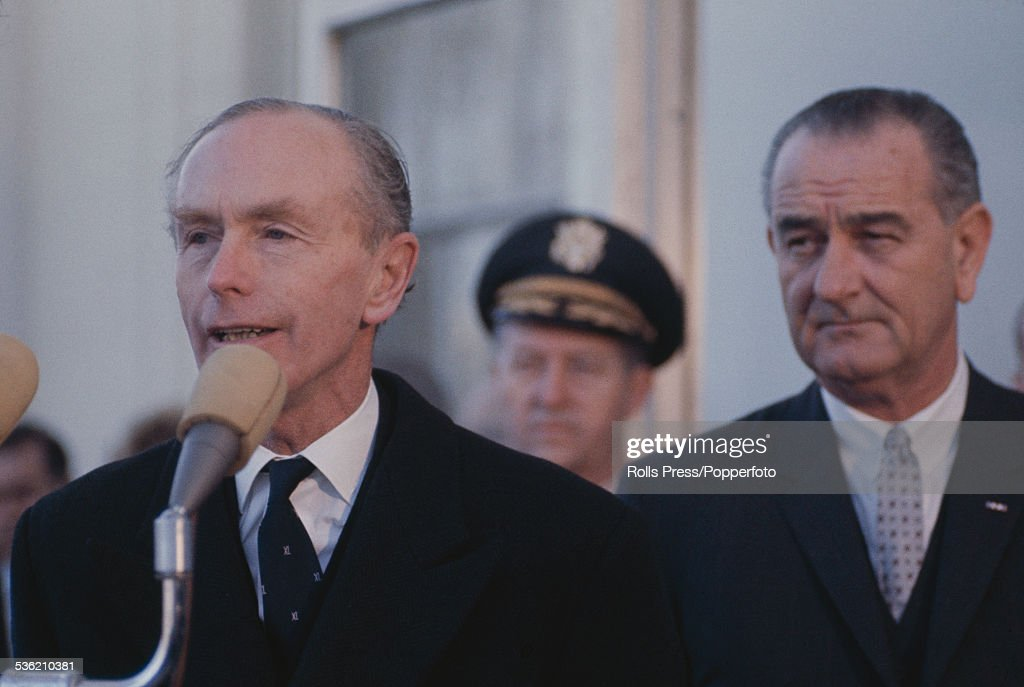 Prime Minister of the United Kingdom, Alec Douglas-Home (1903-1995) talks in to a microphone while President of the United States, Lyndon B. Johnson (1908-1973) observes from right in Washington DC on 14th February 1964.