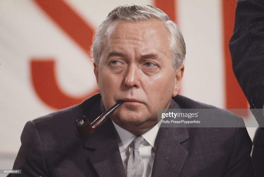 Prime Minister of the United Kingdom, Harold Wilson (1916-1995) sits, smoking a pipe, on the platform at the Labour Party annual conference in Brighton on 5th October 1966.
