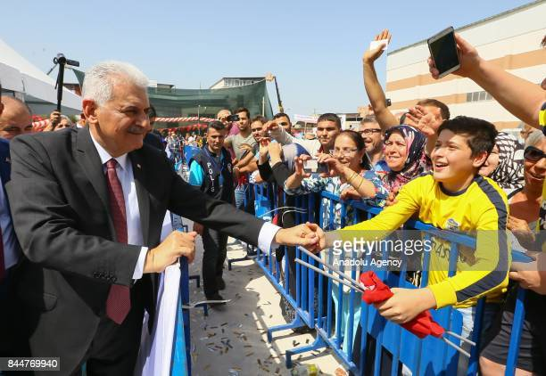 Prime Minister of Turkey Binali Yildirim greets a little kid after the opening ceremony of Buca Yasin Boru Youth Centre and groundbreaking ceremony...