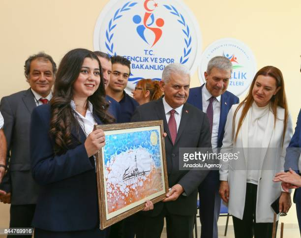 Prime Minister of Turkey Binali Yildirim is received a gift after the opening ceremony of Buca Yasin Boru Youth Centre and groundbreaking ceremony of...