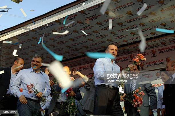 Prime Minister Recep Tayyip Erdogan and Foreign Minister Abdullah Gul throw flowers before speaking to thousands of flagwaving Turks who jammed into...