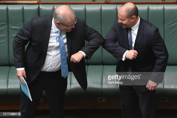 Prime Minister Scott Morrison react with Treasurer Josh Frydenberg after the Coronavirus Economic Response Bill was presented in the House of...