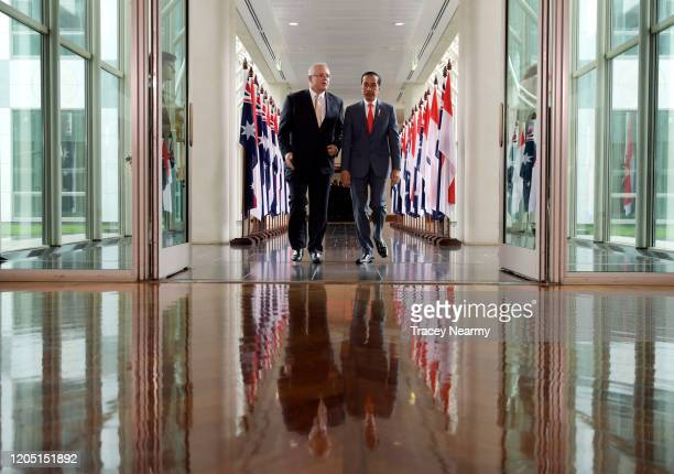 Prime Minister Scott Morrison walks with Indonesian President Joko Widodo through a linkway as they leave the House of Representatives at Parliament...