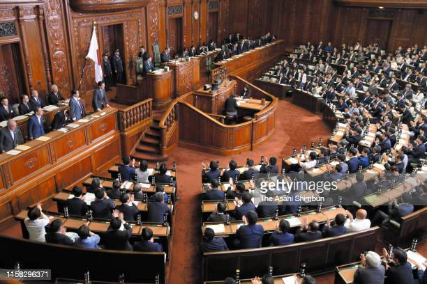 Prime Minister Shinzo Abe and his cabinet members bow as the no-confidence motion is defeated at a lower house plenary session at the Diet building...