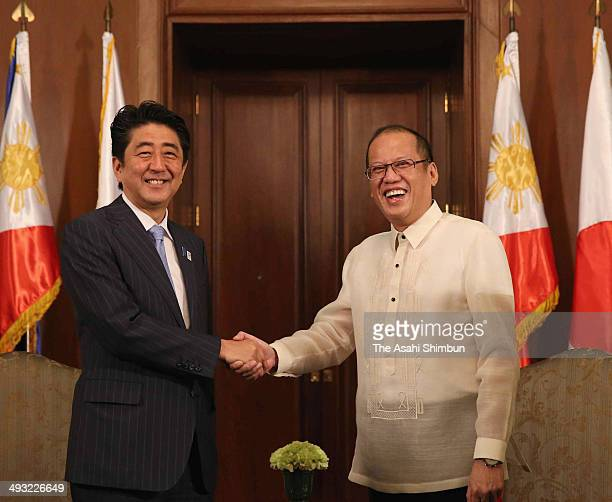 Prime Minister Shinzo Abe and Philippine President Benigno Aquino III shake hands ahead of their meeting on July 27 2013 in Manila Philippines