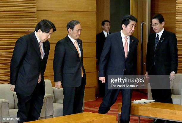 Prime Minister Shinzo Abe arrives to the cabinet meeting while new Agriculture Minister Yoshimasa Hayashi bows at the Abe's official residence on...