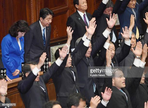 Prime Minister Shinzo Abe bows as lawmakers throw their arms in the air in a customary banzai when the House of Representatives was dissolved on Sept...