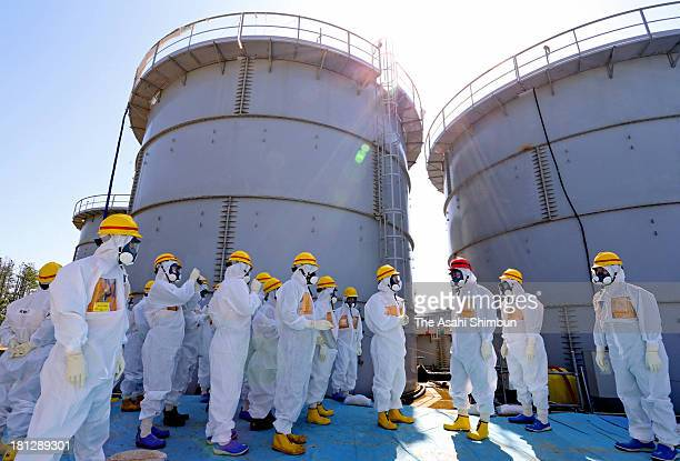 Prime Minister Shinzo Abe in red helmet listens to an explanation about the radationcontaminated water leakage at the Tokyo Electric Power Co...