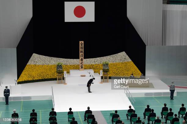 Prime Minister Shinzo Abe of Japan, bows to Emperor Naruhito and Empress Masako during a memorial service marking the 75th anniversary of Japan's...
