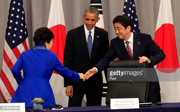 Prime Minister Shinzo Abe of Japan greets President Park Geun-Hye of the Republic of Korea as President Barack Obama looks on during a meeting at the...