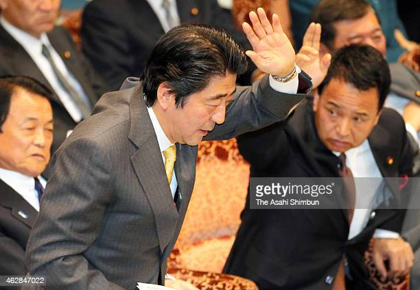 Prime Minister Shinzo Abe raises his hand to answer a question during an audit committee of upper house at the diet building on February 6 2015 in...