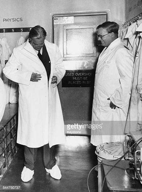 Prime Minister Sir Anthony Eden putting on protective clothing for a tour of Aldermaston Atomic Weapons Research Establishment with Director Sir...