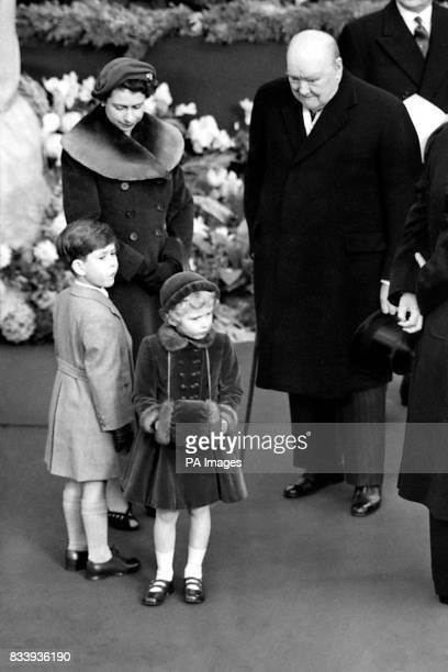 Prime Minister Sir Winston Churchill beams down upon Princess Anne her hands demurely folded in a velvet muff as she waited with her mother Queen...