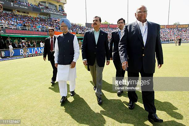 Prime Minister Syed Yusuf Raza Gilani of Pakistan and Prime Minister Manmohan Singh of India walk to greet the teams prior to the start of the 2011...