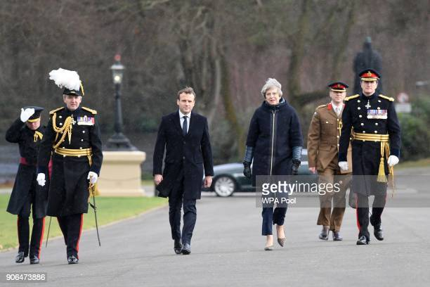 Prime Minister Theresa May and French President Emmanuel Macron arrive to view a guard of honour ahead of UKFrance summit talks at the Royal Military...