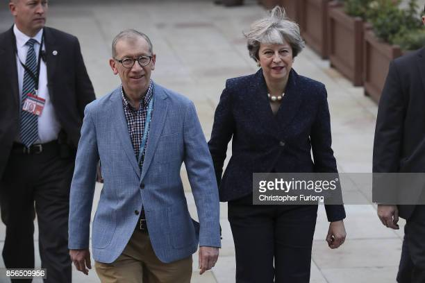 Prime Minister Theresa May and her husband Philip walk across the concourse of Manchester Central at the start of day two of the Conservative Party...