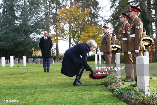 Prime Minister Theresa May as Belgian Prime Minister Charles Michel looks on lays a wreath at the graves of John Parr the first British soldier to be...