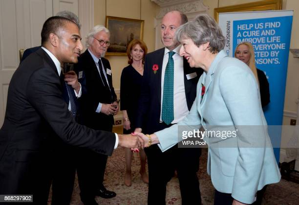 Prime Minister Theresa May greets Adil Ray as Sir Billy Connolly and Jane Asher look on during a reception to mark 200 years since Dr James Parkinson...