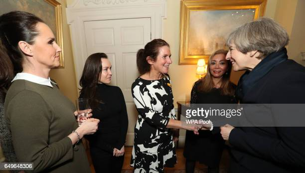 Prime Minister Theresa May greets Rhian Williams Celia Peachey Rhian Burke and Leyla Edwards during an International Women's Day reception at 10...