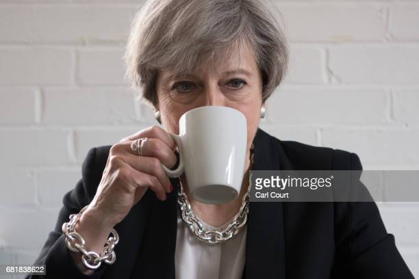 Prime Minister Theresa May has a drink as she chats with youth activists during a visit to the Young Minds mental health charity on May 11 2017 in...