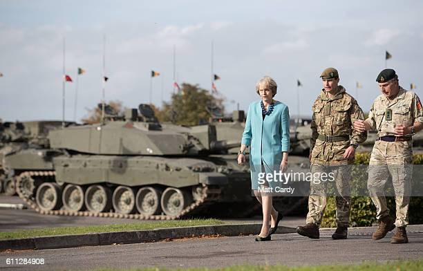 Prime Minister Theresa May passes tanks as she walks with Lt Col Paddy Ginn commander of 1 MERCIAN and General Sir Nicholas Carter Chief of the...