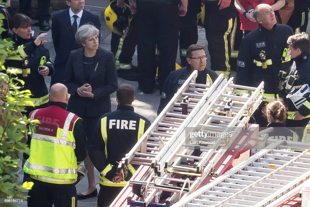 Prime Minister Theresa May speaks to Dany Cotton, Commissioner of the London Fire Brigade, with members of the fire service as she visits Grenfell Tower, on June 15, 2017 in London, England. At least twelve people have been confirmed dead and dozens missing, after the 24 storey residential Grenfell Tower block in Latimer Road was engulfed in flames in the early hours of June 14. The number of fatalities are expected to rise.