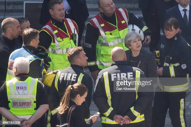 Prime Minister Theresa May speaks to members of the fire service as she visits Grenfell Tower on June 15 2017 in London England At least twelve...