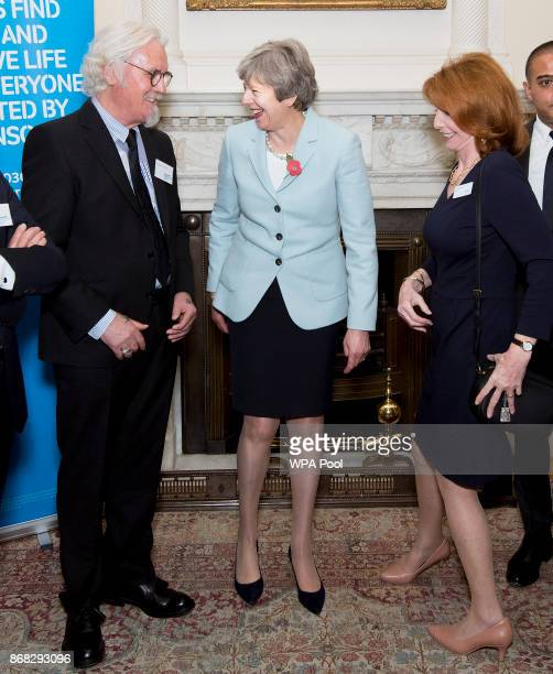 Prime Minister Theresa May speaks with Sir Billy Connolly and Jane Asher during a reception to mark 200 years since Dr James Parkinson published 'An...