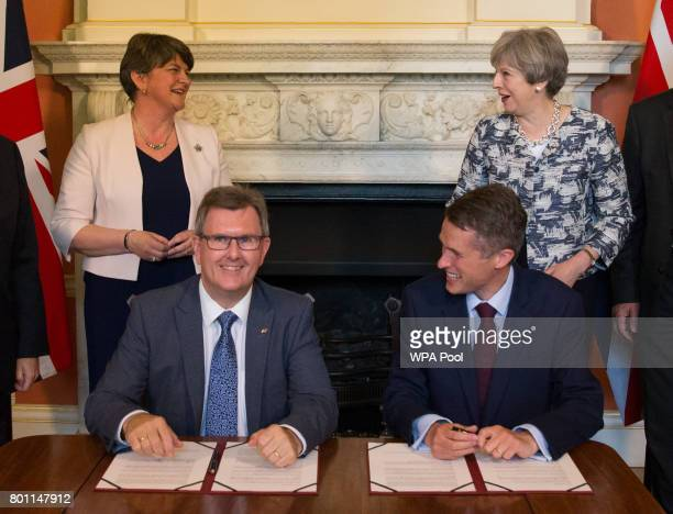 Prime Minister Theresa May stands with Democratic Unionist Party leader Arlene Foster as DUP MP Jeffrey Donaldson and Parliamentary Secretary to the...