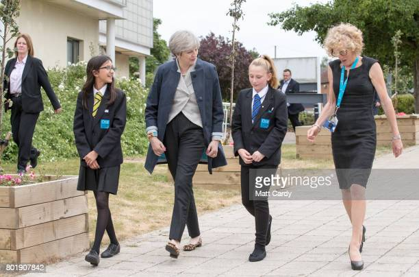 Prime Minister Theresa May walks with pupils Miya Herbert Katie Davies and head teacher Dr Helen Holman as she arrives for a session for teachers...