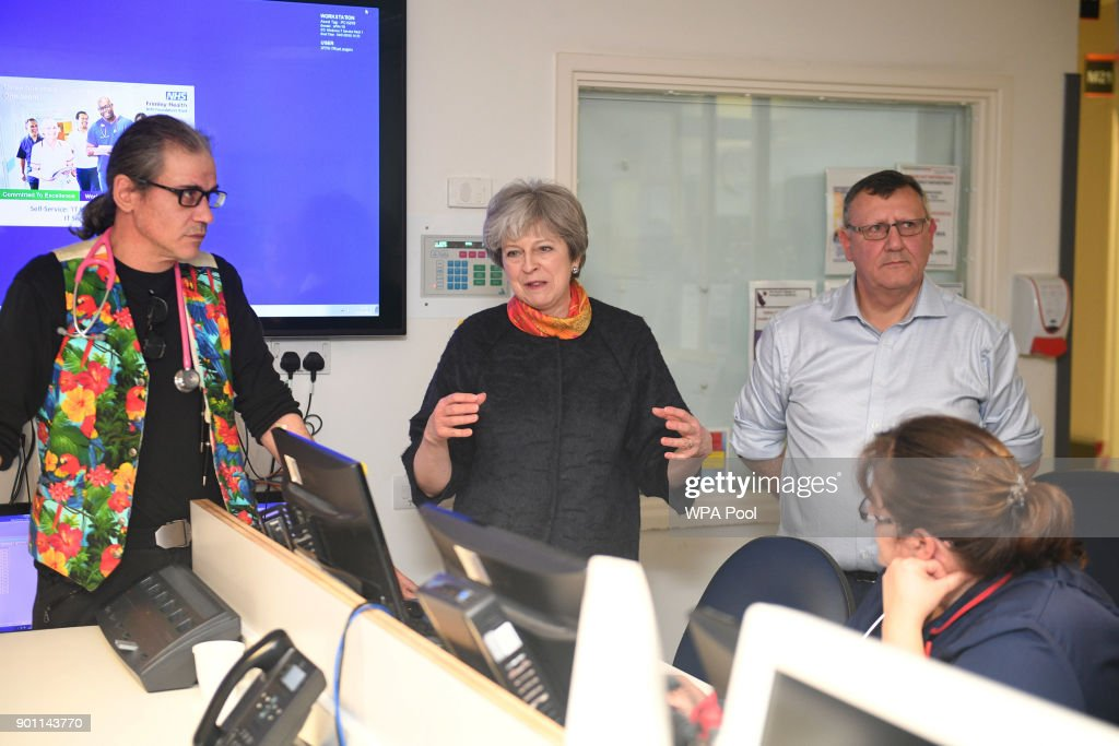 Prime Minister Theresa May (C) with consultant Nick Payne Emergency Sevices Director (L) and Frimley Health CEO Sir Andrew Morris (R) at Frimley Park Hospital on January 4, 2018 in Frimley, England.